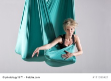 Single athletic woman doing intense leg and hip stretching exercises wrapped in aerial yoga blanket suspended from ceiling