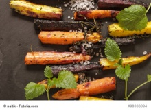 baked colorful carrots on a black background